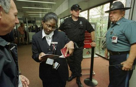 American Airlines ticket agent Michelle Abel is surrounded by added security as she checks a passenger's ticket and identification inside terminal B at Logan International Airport in Boston Tuesday, Sept. 18, 2001, one week after two Boston-based passenger aircraft were hijacked and crashed into the World Trade Center towers in New York. (AP Photo/Gretchen Ertl) 10logan airlinegallery